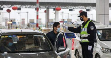 Un policía usa un termómetro digital para chequear la temperatura de un automovilista en un punto de peajes en una carretera en Wuhan