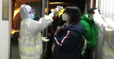 Funcionarios de salud revisan la temperatura corporal de los pasajeros que llegan de la ciudad de Wuhan al aeropuerto de Beijing